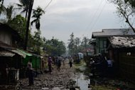 Muslim Rohingyas walk down the main road in the Aung Mingalar quarter, turned into a ghetto after violence wracked the city of Sittwe, capital of Myanmar's western Rakhine state