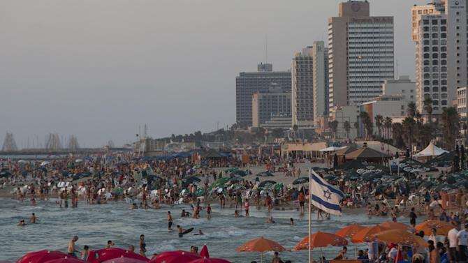 FILE - In this Friday, Aug. 10, 2012 file photo, people  enjoy the Mediterranean Sea in Tel Aviv, Israel. The freewheeling seaside oasis of Tel Aviv has long served as an escape from the troubles of everyday Israel. Thanks partly to its vibrant nightlife and balmy climate, it's also developed an international reputation as a fun place to visit _ and one of the few places in the Middle East where gays feel free to walk hand-in-hand and kiss in public. In the tech industry, the bustling metropolis is known as a hub of innovative companies. Now, for the first time ever, Tel Aviv is also the target of Iranian-made rockets fired by Hamas militants in the Gaza Strip. (AP Photo/Ariel Schalit, File)