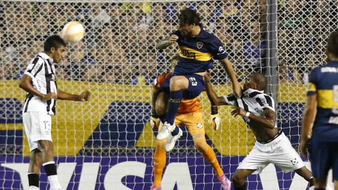 Osvaldo of Argentina's Boca Juniors heads the ball past Olivera and Silva of Uruguay's Wanderers during Copa Libertadores soccer match in Buenos Aires