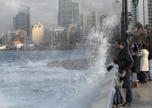 Lebanese citizens watch waves break at the Corniche wall, in Beirut, Lebanon, on Sunday Jan. 8, 2012. Lebanon is under the effects of a rain storm and according to the Lebanese meteorology a snow storm will hit Mount Lebanon on Wednesday. (AP Photo/Hussein Malla)