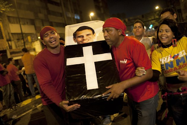 Supporters of Venezuela's President Hugo Chavez perform a mock funeral for opposition candidate Henrique Capriles as they celebrate in downtown Caracas, Venezuela, Sunday, Oct. 7, 2012.  Chavez won re