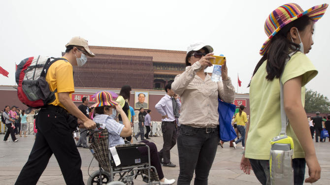 In this Tuesday, May 7, 2013 photo, visitors to Tiananmen Gate wear masks during a day of heavy pollution in Beijing. Air pollution significantly shortens people's life expectancy, according to a study published Tuesday that says bad air shortened the lives of 500 million people in north China by an average of more than five years. (AP Photo/Ng Han Guan)