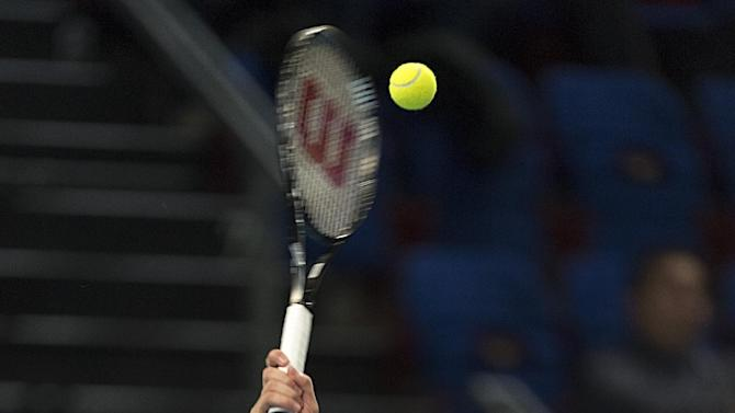 Canada's Milos Raonic serves to Belgium's David Goffin during their quarter final match at the Swiss Indoors tennis tournament at the St. Jakobshalle in Basel, Switzerland, Friday, Oct. 24, 2014. (AP Photo/Keystone, Georgios Kefalas)