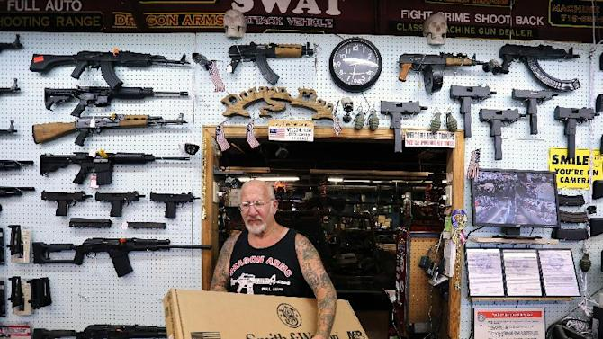 In this July 20, 2014 photo, gun dealer Mel Bernstein carries box for a rifle while making a sale at his store, Dragonman's, east of Colorado Springs, Colo. When Colorado lawmakers expanded background checks on firearms last year, they were expecting a huge increase. But the actual number the first 12 months of the law is far lower than projected, according to an analysis of state data by The Associated Press. (AP Photo/Brennan Linsley)