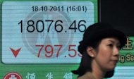 A woman walks past a display board showing the Hang Seng stock market index in Hong Kong, 2011. Asian markets fell and the euro sat near multi-year lows amid growing fears Spain will need a full bailout, while tech shares were hit by Apple&#39;s disappointing earnings report