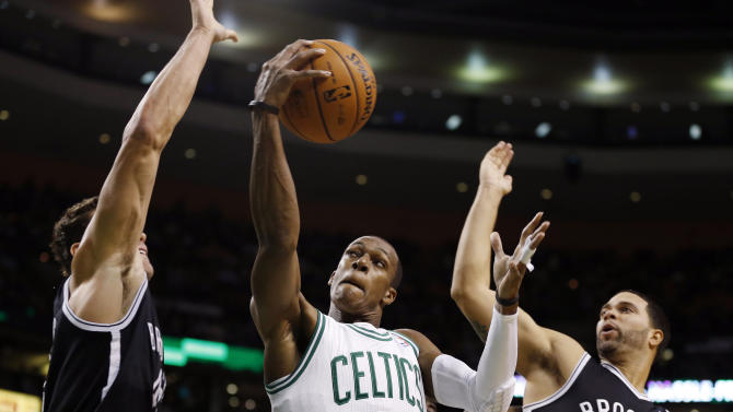Boston Celtics' Rajon Rondo (9) goes up to shoot between Brooklyn Nets' Kris Humphries, left, and Deron Williams (8) in the first quarter of an NBA basketball game in Boston, Wednesday, Nov. 28, 2012. (AP Photo/Michael Dwyer)