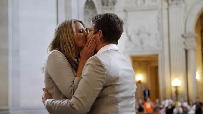 Sandy Stier, left, kisses Kris Perry after they were wed by California Attorney General Kamala Harris at City Hall in San Francisco, Friday, June 28, 2013. Stier and Perry, the lead plaintiffs in the U.S. Supreme Court case that overturned California's same-sex marriage ban, tied the knot about an hour after a federal appeals court freed same-sex couples to obtain marriage licenses for the first time in 4 1/2 years. (AP Photo/Marcio Jose Sanchez)