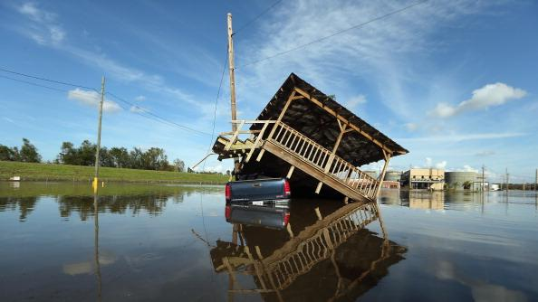 A partially submerged truck and gazebo are seen in Hurricane Isaac's flood waters with a flooded chemical plant in the background on September 1, 2012 in Braithwaite, Louisiana. Louisiana residents continue to cope with the aftermath of Hurricane Isaac with ongoing flooding, destroyed property and many still without electricity. (Photo by Mario Tama/Getty Images)