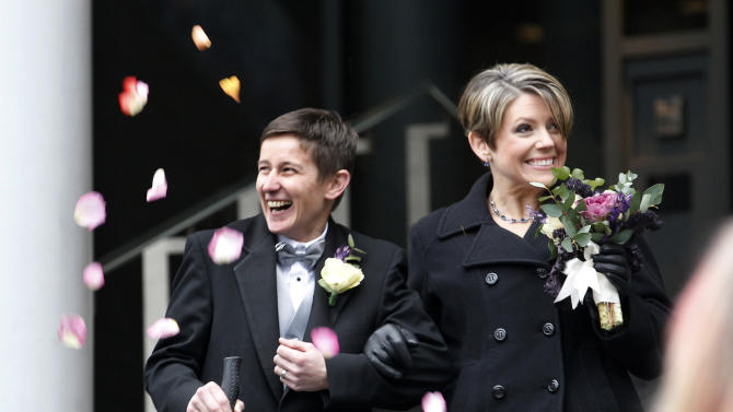 Newlyweds Heather Laird, left, and Dawn Rains smile as flower petals are tossed their way as they depart Seattle City Hall, Sunday, Dec. 9, 2012, in Seattle. Gov. Chris Gregoire signed a voter-approved law legalizing gay marriage Wednesday, Dec. 5, and weddings for gay and lesbian couples began in Washington state on Sunday, following the three-day waiting period after marriage licenses were issued earlier in the week. (AP Photo/Elaine Thompson)