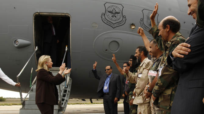 U.S. Secretary of State Hillary Rodham Clinton  claps as she meets Libyan soldiers at the steps of her C-17 military transport upon her arrival in Tripoli Libya, Tuesday Oct. 18, 2011. The Obama administration on Tuesday increased U.S. support for Libya's new leaders as Secretary of State Hillary Rodham Clinton made an unannounced visit to Tripoli and pledged millions of dollars in new aid, including medical care for wounded fighters and additional assistance to secure weaponry that many fear could fall into the hands of terrorists.  (AP Photo/Kevin Lamarque, Pool)