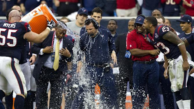 Houston Texans coach Gary Kubiak, center, is doused by Chris Myers (55) as Arian Foster (23) reacts during the fourth quarter of an NFL football game against the Indianapolis Colts, Sunday, Dec. 16, 2012, in Houston. The Texans defeated the Colts 29-17. (AP Photo/Houston Chronicle,  Brett Coomer)  MANDATORY CREDIT