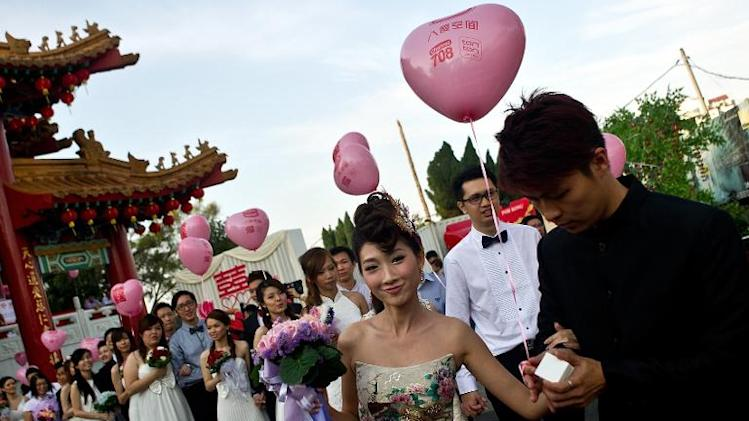 A newly-wed ethnic Malaysian-Chinese couple walks out during their mass wedding ceremony on Valentine's Day at the Thean Hou Temple in Kuala Lumpur on February 14, 2014