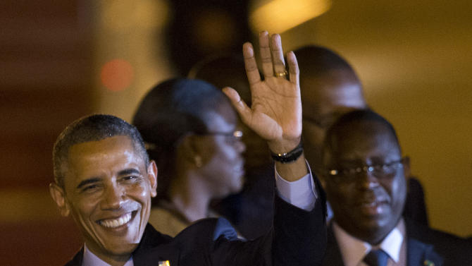U.S. President Barack Obama, standing beside Senegalese counterpart Macky Sall, waves as he boards a car after arriving at the airport in Dakar, Senegal, Wednesday, June 26, 2013. President Obama opened a weeklong trip to Africa on Wednesday, a three-country visit aimed at overcoming disappointment on the continent over the first black U.S. president's lack of personal engagement during his first term. (AP Photo/Rebecca Blackwell)