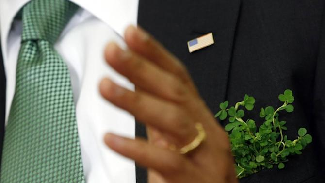 Wearing a green tie and with shamrock in his pocket, President Barack Obama makes a statement to reporters during his meeting with Irish Prime Minister Enda Kenny in the Oval Office of the White House in Washington, Tuesday, March 19, 2013. (AP Photo/Charles Dharapak)