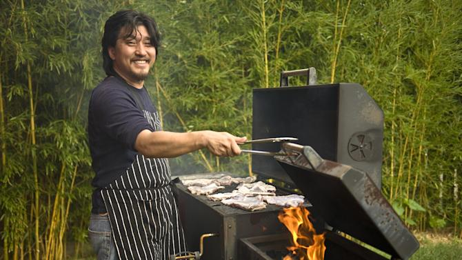 "In this June 2012 publicity photo provided by Artisan Books, Chef Edward Lee grills lamb in Louisville, K.Y. Lee recommends lamb barbecue for its smokiness and simplicity in his book, ""Smoke & Pickles,"" published by Artisan Books.  AP Photo/Artisan Books, Grant Cornett)"