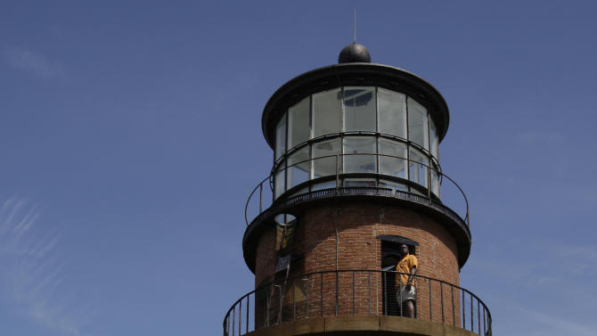 FILE - In this Aug. 27, 2009, file photo, President Barack Obama, left, walks around Gay Head Lighthouse while on vacation on Martha's Vineyard in Aquinnah, Mass. The Gay Head Lighthouse, a 160-year-old beacon that's among the most endangered historic landmarks in the United States, is expected to begin a multi-day trek inland from its rapidly eroding cliffside perch on Thursday, May 28, 2015. (AP Photo/Alex Brandon, File)