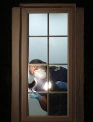 A British police crime scene investigator examines the interior of a window inside the home of a family shot dead in their car in the French Alps in Claygate, in south-east England, on September 8, 2012