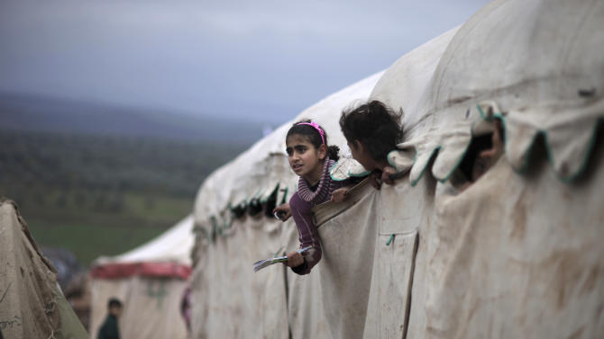 In this Monday, Dec. 10, 2012 photo, Syrian girls who fled their homes with their families peek out of their makeshift school at a camp for displaced Syrians in the village of Atmeh, Syria. This tent camp sheltering some of the hundreds of thousands of Syrians uprooted by the country's brutal civil war has lost the race against winter: the ground under white tents is soaked in mud, rain water seeps into thin mattresses and volunteer doctors routinely run out of medicine for coughing, runny-nosed children. (AP Photo/Muhammed Muheisen)