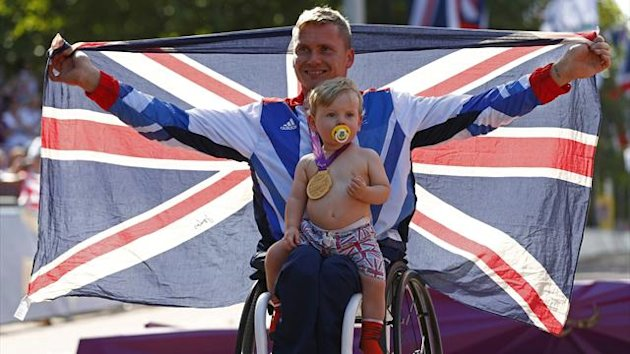 Britain's David Weir poses for a photograph with his son Mason, after being presented with the gold medal for winning the Men's Marathon T54 classification during the London 2012 Paralympic Games September 9, 2012 (Reuters)