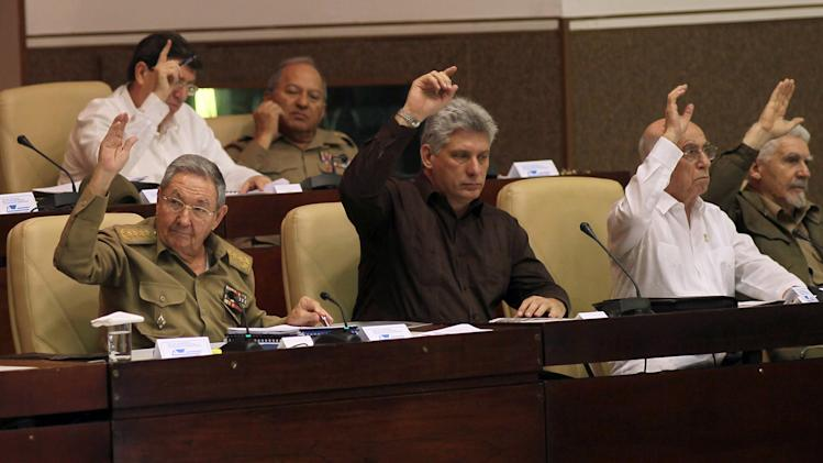 Cuba's Vice-President Miguel Diaz-Canel, center, Cuba's President Raul Castro, left, First Vice-President of the Council of State Jose Ramon Machado Ventura, second from right, and Commander of the Cuban Revolution Ramiro Valdes, right, raise their hands to vote the foreign investment law during an extraordinary session at the National Assembly in Havana, Cuba, Saturday, March. 29, 2014. Cuban lawmakers approved a law Saturday that aims to make it more attractive for foreign investors to do business in and with the country, a measure seen as vital if the island's struggling economy is to improve. IN the back row, also voting, Foreign Minster Bruno Rodrigues, left, and Defense Minister Leopoldo Cintas Frias, right. (AP Photo/Ismael Francisco, Cubadebate)