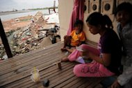A Cambodian woman and her children sitting outside their house in 2011. An unidentified disease has killed 60 young children in Cambodia in three months, the World Health Organization said Tuesday as it raced to identify the cause