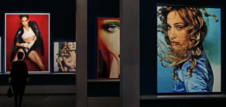 "A woman walks past a large portrait of Jennifer Lopez, left, by photographer Mario Testino during the preview of his shows ""In Your Face"" and ""British Royal Portraits"" at the Museum of Fine Arts in Boston, Wednesday, Oct. 17, 2012.  At right is a portrait of Madonna. (AP Photo/Charles Krupa)"