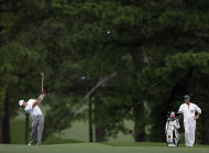 Caddie Billy Foster watches Lee Westwood, of England, hits his second shot on the 17th fairway during the first round the Masters golf tournament Thursday, April 5, 2012, in Augusta, Ga. (AP Photo/David J. Phillip)