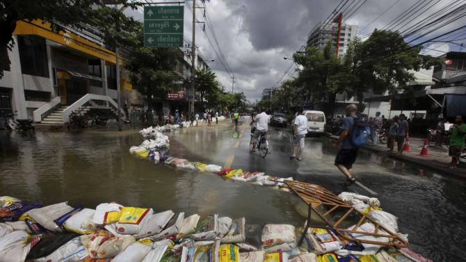 Floodwater gushes into a manhole in the middle of a street in Bangkok, Thailand, Saturday, Oct. 29, 2011. Defenses shielding the center of Thailand's capital from the worst floods in nearly 60 years mostly held at critical peak tides Saturday, but areas along the city's outskirts remained submerged along with much of the countryside. (AP Photo/Altaf Qadri)