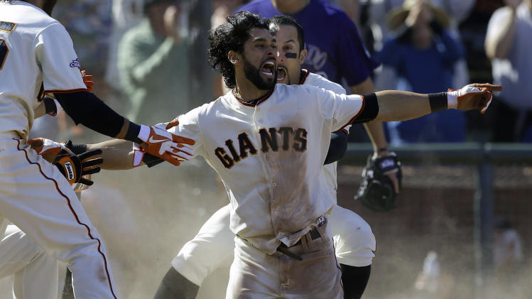 San Francisco Giants' Angel Pagan, center foreground, celebrates with Andres Torres after hitting an inside-the-park two-run home run off Colorado Rockies pitcher Rafael Betancourt during the tenth inning of a baseball game in San Francisco, Saturday, May 25, 2013. The Giants won 6-5. (AP Photo/Jeff Chiu)