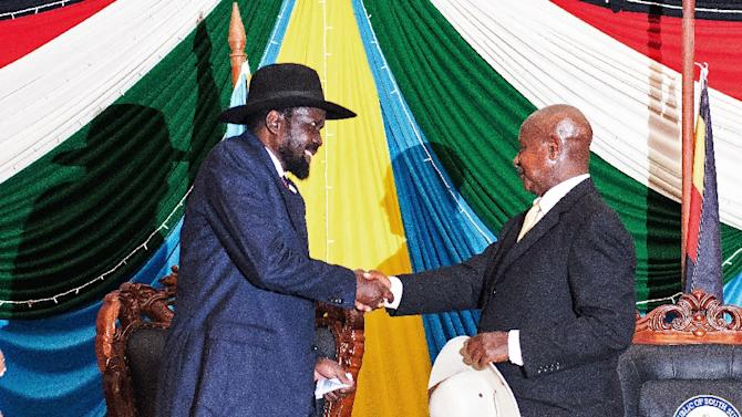 South Sudan's President Salva Kiir (L) shakes hands with Uganda's President Yoweri Museveni (R) after signing a peace agreement to end 20 months of war in the world's youngest nation, August 26, 2015 in Juba