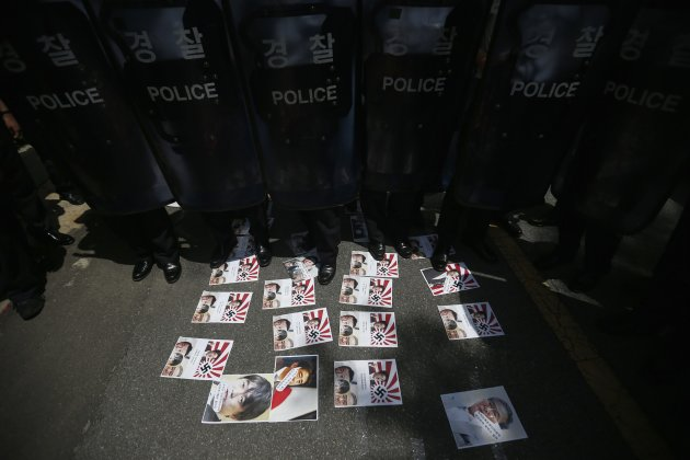South Korean police stand guard against protesters as posters depicting Japan's Prime Minister Abe and the rising sun flag, are seen in front of the official residence of the Japanese ambassador durin