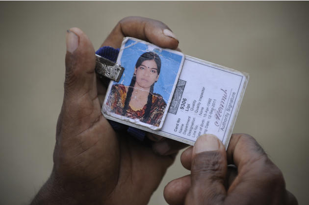 A man holds his daughter's photo and ID card which she used while working at a garment factory which collapsed last week in Savar near Dhaka, Bangladesh, Sunday, May 5, 2013. Police said more than 600