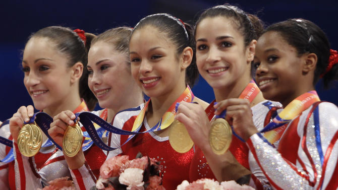 USA's gymnasts, from left, Jordyn Wieber, McKayla Maroney, Sabrina Vega, Alexandra Raisman and Gabrielle Douglas, celebrate on the podium winning the women's team final at  the Artistic Gymnastics World Championships in Tokyo, Japan, Tuesday, Oct. 11, 2011. (AP Photo/Bullit Marquez)