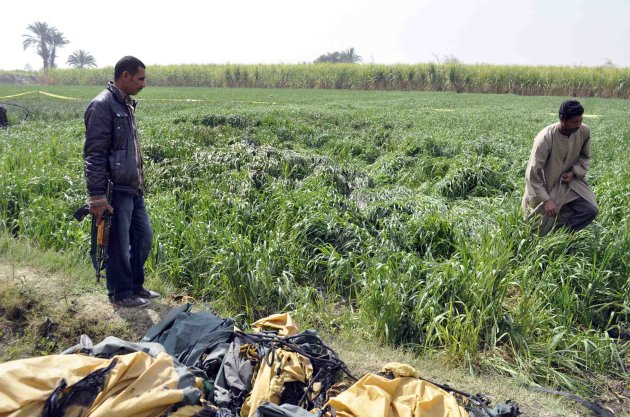 A security officer and a rescue official examine the wreckage of a hot air balloon that crashed in Luxor