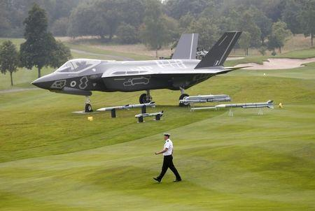 A member of the Royal Navy walks past a model of a F-35 on the fairway at Celtic Manor golf club near Newport in Wales