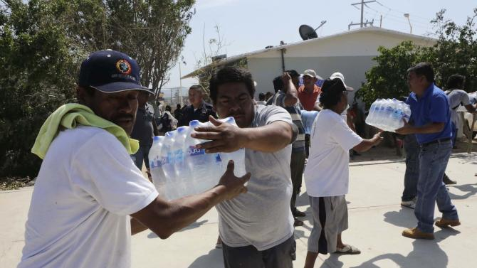 Residents carry bottles of water in a school used as a shelter in Cabo San Lucas, after Hurricane Odile hit in Baja California