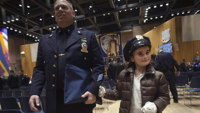 Karen Tanner, daughter of Nick Tanner, tries on his hat and gloves after her father was promoted to the rank of Detective Specialist in the Manhattan borough of New York