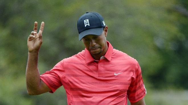 Tiger Woods acknowledges the crowd after sinking his putt for birdie on the second green during the final round of the Arnold Palmer Invitational golf tournament in Orlando, Fla., Sunday, March 24, 2013. (AP Photo/Phelan M. Ebenhack)