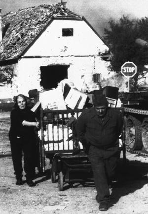 "FILE - The Nov. 10, 1991 file photo shows Serbian residents of the medieval city of Vukovar fleeing with a carriage full of their personal belongings from what remains of their home, which was destroyed during heavy fighting between Yugoslav federal army troops and Croatian security forces. Thousands are expected to join a protest on Saturday, Feb. 2, 2013 organized by the veteran groups, Vukovar wartime defenders and hardline political parties. Opponents of the Serbian script have been active on Facebook, where one of the postings reads: ""The final strike on Vukovar _ Cyrillic!""   More than twenty years after it was reduced to rubble in a Serb army siege, Vukovar is testing the Croatian government's European Union agenda in a former war zone that is to become the bloc's eastern edge when Croatia joins as 28th member on July 1. War wounds have been revived by the Croatian government bid to introduce Serbian Cyrillic the areas with sizable Serb community _ including Vukovar _ a move that is in line with the EU's standards for the respect of minority rights, but which has infuriated war veterans and nationalists. (AP Photo/file)"