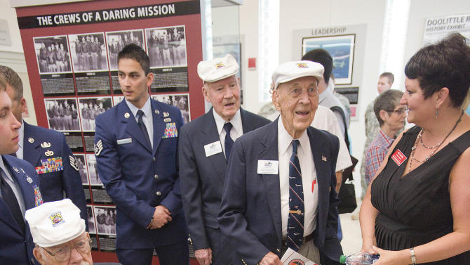 Doolittle Raiders, in white caps, left to right, Edward J. Saylor, David J. Thatcher and Richard E. Cole view the new Doolittle Raiders exhibit with facilities coordinator Mia Checkley , far right, Wednesday morning April 17, 2013 at Northwest Florida State College in Niceville, Fla. The Doolittle Tokyo Raid was a notable attack on the Japanese during World War II using B-25's.  (AP Photo/Northwest Florida Daily News, Mark Kulaw)