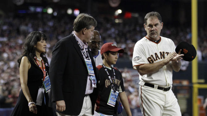 From left, Roxanna Green walks with her husband John Green and their son Dallas along with American League manager Ron Washington of the Texas Rangers and National League manager Bruce Bochy, right, of the San Francisco Giants during the playing of the national anthem the MLB All-Star baseball game Tuesday, July 12, 2011, in Phoenix. (AP Photo/David J. Phillip)