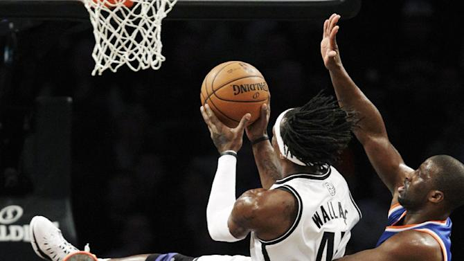 Brooklyn Nets forward Gerald Wallace (45) goes up for a layup as New York Knicks guard Raymond Felton (2) and forward Carmelo Anthony (7) defend in the first half of their NBA basketball game at Barclays Center, Tuesday, Dec. 11, 2012, in New York. (AP Photo/Kathy Willens)