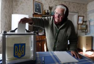 Local resident places her ballot into a mobile ballot box during a parliamentary election, at her home in Horodyshche near Chernihiv