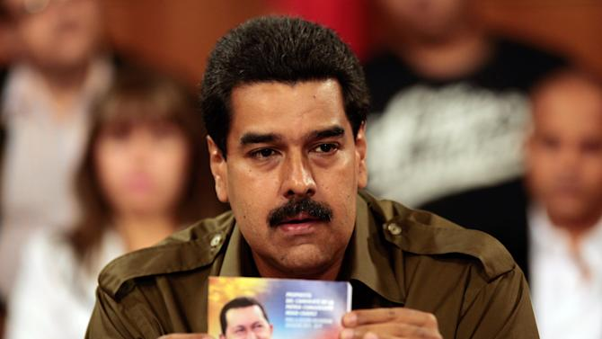 """In this photo released by Miraflores Press Office, Venezuela's acting President Nicolas Maduro holds a printed photo of late President Hugo Chavez during a televised speech from Miraflores presidential palace in Caracas, Venezuela, Monday, March 18, 2013. Maduro said Venezuela will launch a """"complementary"""" foreign exchange system to facilitate the supply of U.S. dollars to priority sectors of the economy. (AP Photo/Miraflores Press Office)"""