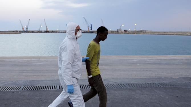 A staff member walks with a migrant after disembarkment in the Sicilian harbour of Augusta