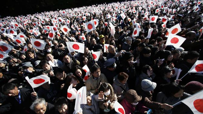Well-wishers wave Japanese national flags to celebrate Japan's Emperor Akihito's 81st birthday at Imperial Palace in Tokyo