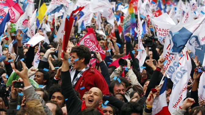 Supporters of Socialist Party candidate for the presidential election Francois Hollande react after the first results of the second round of French presidential elections outside Socialist Party campaign headquarters in Paris, France, Sunday, May 6, 2012.  First results show that Hollande had won the election.  (AP Photo/Francois Mori)