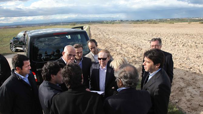"FILE - In this photo released by the Madrid Regional Government on May 6,  2012,  CEO of Las Vegas Sands Corp. Sheldon Adelson, centre with sunglasses, talks with delegates while visiting Alcorcon on the outskirts of Madrid. Las Vegas Sands casinos and Madrid officials have chosen the town of Alcorcon on the outskirts of the Spanish capital as the site for the multi-billion dollar ""EuroVegas"" casino project, which authorities hope will bring much needed jobs and investment to the recession-wracked country. The announcement made Friday Feb. 8, 2013 stated that the entire project, initially comprising 12 hotels and six casinos, is to be finished by 2023 at an estimated cost of euro 22 billion. Las Vegas Sands is to fund 35 percent of the project. It is not clear where the remaining 65 percent will come from. Spain has a swollen deficit and 26 percent unemployment. (AP Photo/Comunidad de Madrid, File)"