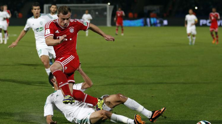 Xherdan Shaqiri of Germany's Bayern Munich trips over Mohamed Oulhaj of Morocco's Raja Casablanca during their 2013 FIFA Club World Cup final soccer match at Marrakech stadium