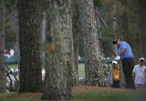 U.S. golfer Kevin Stadler hits a shot from the trees on the first hole during the final round of the Masters golf tournament at the Augusta National Golf Club in Augusta